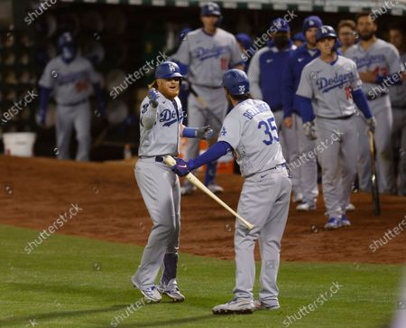 Stock Image of Los Angeles Dodgers Justin Turner (L) is greeted by Los Angeles Dodgers Cody Bellinger (R) after hitting a solo home run against the Oakland Athletics during the eighth inning of their MLB game at the Oakland Coliseum in Oakland, California, USA, 05 April 2021.