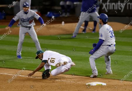 Los Angeles Dodgers Cody Bellinger (R) safe at first on a single while colliding with Oakland Athletics relief pitcher Reymin Guduan (C) after the Dodgers challenge the call during the ninth inning of their MLB game at the Oakland Coliseum in Oakland, California, USA, 05 April 2021. Both players left the game with injuries.