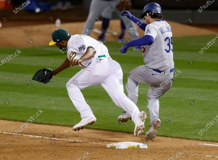 Stock Photo of Los Angeles Dodgers Cody Bellinger (R) safe at first on a single while colliding with Oakland Athletics relief pitcher Reymin Guduan (L) after the Dodgers challenge the call during the ninth inning of their MLB game at the Oakland Coliseum in Oakland, California, USA, 05 April 2021. Both players left the game with injuries.