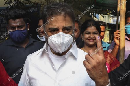 Makkal Needhi Maiam party leader and film actor Kamal Haasan displays his ink mark after casting his vote in the Tamil Nadu state assembly elections in Chennai, India