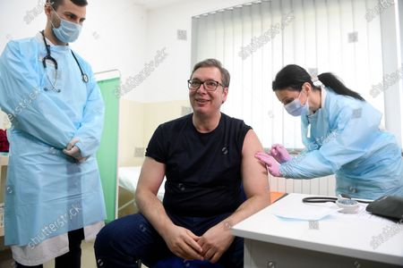 In this photo provided by the Serbian Presidential Press Service, Serbian President Aleksandar Vucic, centre, receives a dose of the Chinese Sinopharm vaccine in the village of Rudna Glava, Serbia, . Vucic finally rolled up his sleeve for a coronavirus vaccine Tuesday and to encourage his country's increasingly skeptical Serbs to get vaccinated themselves