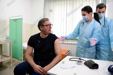 In this photo provided by the Serbian Presidential Press Service, Serbian President Aleksandar Vucic, left speaks with medics before receiving a dose of the Chinese Sinopharm vaccine in the village of Rudna Glava, Serbia, . Vucic finally rolled up his sleeve for a coronavirus vaccine Tuesday and to encourage his country's increasingly skeptical Serbs to get vaccinated themselves