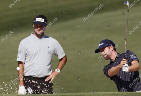Bubba Watson (L) watches as Webb Simpson (R) hits from the bunker on the second fairway during a practice round for the 2021 Masters Tournament at the Augusta National Golf Club in Augusta, Georgia, USA, 06 April 2021. The 2021 Masters Tournament is held 08 April through 11 April 2021.