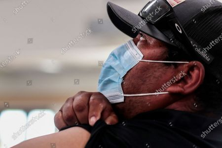Bell, CA, Monday, April 5, 2021 - Victor Joaquin rolls up his sleeve moments before receiving a Covid-19 vaccination at the Bell Community Center. (Robert Gauthier/Los Angeles Times)