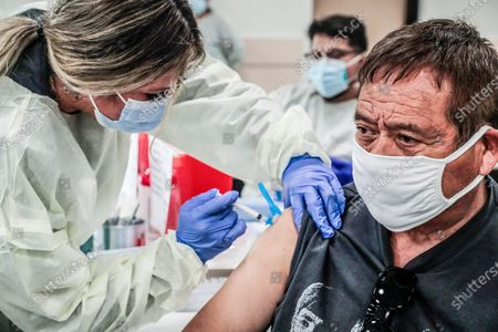 Stock Image of Bell, CA, Monday, April 5, 2021 - Medcial tech Janette Serrano injects Henry Perez, 71, with a Covid-19 vaccine are offered at the Bell Community Center. (Robert Gauthier/Los Angeles Times)