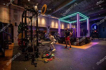 Stock Photo of A large neon-lit DJ booth, right, in the center of the gym at John Reed Fitness on Monday, April 5, 2021 in downtown Los Angeles, CA. (Brian van der Brug / Los Angeles Times)