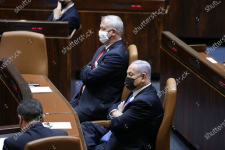Israeli Prime Minister Benjamin Netanyahu, right, Defense Minister Benny Gantz, center, and other lawmakers attend the swearing-in ceremony for Israel's 24th government, at the Knesset, or parliament, in Jerusalem, . The ceremony took place shortly after the country's president asked Netanyahu to form a new majority coalition, a difficult task given the deep divisions in the fragmented parliament