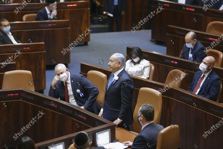 Israeli Prime Minister Benjamin Netanyahu, center, and Defense Minister Benny Gantz, center left, and other lawmakers attend the swearing-in ceremony for Israel's 24th government, at the Knesset, or parliament, in Jerusalem, . The ceremony took place shortly after the country's president asked Netanyahu to form a new majority coalition, a difficult task given the deep divisions in the fragmented parliament