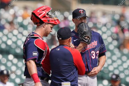 Minnesota Twins pitching coach Wes Johnson talks to starting pitcher J.A. Happ (33) during the fourth inning of a baseball game against the Detroit Tigers, in Detroit