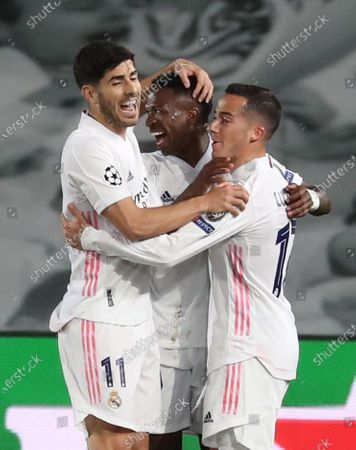 Real Madrid's striker Vinicius Jr (C) celebrates with teammates Marco Asensio (L) and Lucas Vazquez (R) after scoring the 1-0 goal during the UEFA Champions League quarter final first leg soccer match between Real Madrid and Liverpool FC held at Alfredo Di Stefano stadium, in Madrid, central Spain, 06 April 2021.