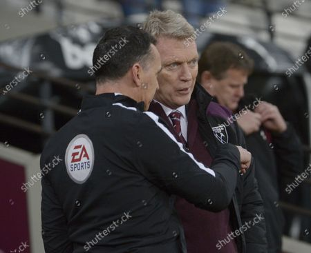 David Moyes of West Ham United speaks with Neil Swarbrick (L) the Fourth Official prior to the Premier League match between West Ham United and West Bromwich Albion at London Stadium on January 2, 2018 in London, England.