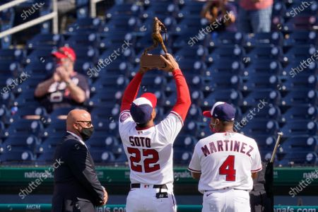 Stock Image of Washington Nationals right fielder Juan Soto (22) holds up his 2020 National League batting title trophy alongside general manager Mike Rizzo, left, and manager Dave Martinez before an opening day baseball game against the Atlanta Braves at Nationals Park, in Washington