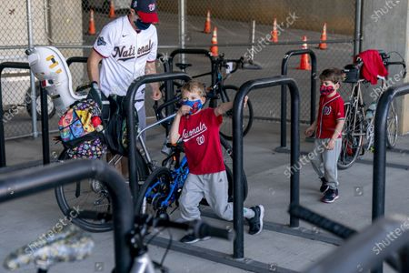 Michael Hoffman of Washington and his sons Evan, 6, center, and Andrew, 4, right, lock up their bikes as they arrive before the Washington Nationals play the Atlanta Braves in their opening day baseball game at Nationals Park, in Washington