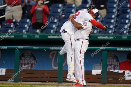 Washington Nationals' Juan Soto, left, celebrates with manager Dave Martinez after Soto hit a game-winning single in the ninth inning of an opening day baseball game against the Atlanta Braves at Nationals Park, in Washington. Victor Robles scored on the play, and Washington won 6-5