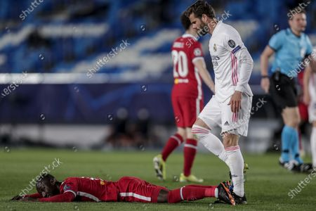 Liverpool's Naby Keita lies on the ground next to Real Madrid's Nacho during the Champions League quarterfinal first leg, soccer match between Real Madrid and Liverpool at the Alfredo di Stefano stadium in Madrid, Spain