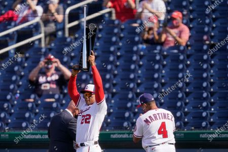 Washington Nationals right fielder Juan Soto (22) holds up his 2020 Silver Slugger Award alongside general manager Mike Rizzo, left, and manager Dave Martinez before an opening day baseball game against the Atlanta Braves at Nationals Park, in Washington