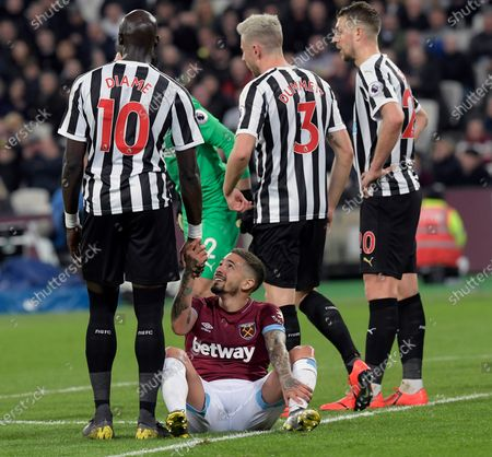 Manuel Lanzini (2nd L) of West Ham United looks up at Mohamed Diame of Newcastle United after being caught on the head by his knee during the Premier League match between West Ham United and Newcastle United at London Stadium on March 2, 2019 in London, United Kingdom.
