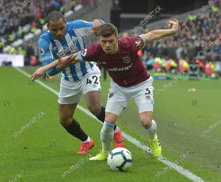 Aaron Cresswell of West Ham United in action with Jason Puncheon of Huddersfield Town during the Premier League match between West Ham United and Huddersfield Town at London Stadium on March 16, 2019 in London, United Kingdom.