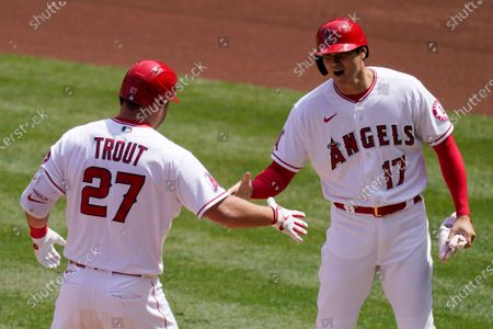 Los Angeles Angels' Mike Trout, left, is congratulated by Shohei Ohtani after hitting a two-run home run during the first inning of a baseball game against the Houston Astros, in Anaheim, Calif