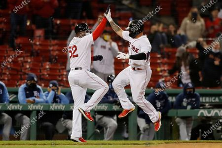Boston Red Sox's Christian Vazquez celebrates his solo home run with third base coach Carlos Febles (52) during the ninth inning of a baseball game against the Tampa Bay Rays, in Boston