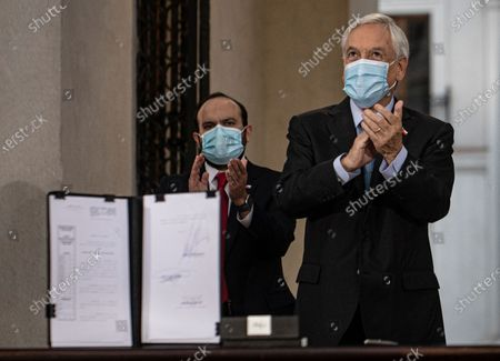 Chile's President Sebastian Pinera applauds after signing the constitutional reform that postpones the next elections for constitutional delegates, mayor's and regional elections for May 15 and 16, due to the COVID-19 pandemic, at a La Moneda presidential palace in Santiago, Chile