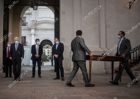 Chile's President Sebastian Pinera, left, looks on as two workers bring in a table for him to sign the constitutional reform that postpones the next elections for constitutional delegates, mayor's and regional elections for May 15 and 16, due to the COVID-19 pandemic, at a La Moneda presidential palace in Santiago, Chile
