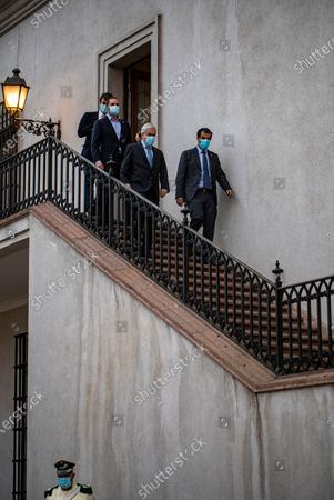 Chile's President Sebastian Pinera, second right, walks down a set of stair with his ministers before signing the constitutional reform that postpones the next elections for constitutional delegates, mayor's and regional elections for May 15 and 16, due to the COVID-19 pandemic, at a La Moneda presidential palace in Santiago, Chile