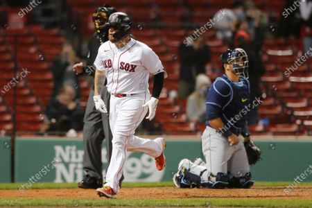 Boston Red Sox's Christian Vazquez celebrates his solo home run as Tampa Bay Rays' Mike Zunino kneels at home plate during the ninth inning of a baseball game, in Boston