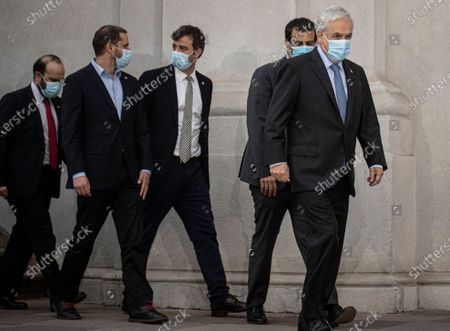 Chile's President Sebastian Pinera, right, walks with his ministers before signing the constitutional reform that postpones the next elections for constitutional delegates, mayor's and regional elections for May 15 and 16, due to the COVID-19 pandemic, at a La Moneda presidential palace in Santiago, Chile