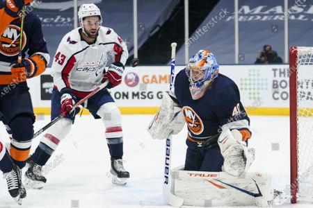 Washington Capitals' Tom Wilson (43) watches as New York Islanders goaltender Semyon Varlamov (40) stops a shot on goal during the first period of an NHL hockey game, in Uniondale, N.Y