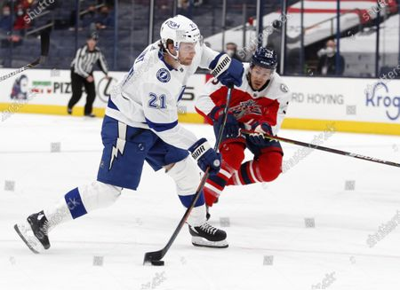 Tampa Bay Lightning forward Brayden Point, left, shoots the puck in front of Columbus Blue Jackets defenseman Michael Del Zotto during the first period of an NHL hockey game in Columbus, Ohio