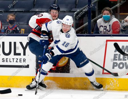 Tampa Bay Lightning forward Ondrej Palat, right, passes the puck in front of Columbus Blue Jackets forward Eric Robinson during the first period of an NHL hockey game in Columbus, Ohio