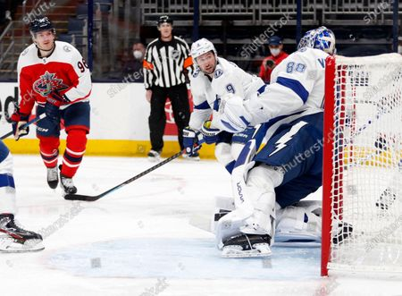 Columbus Blue Jackets forward Jack Roslovic, left, scores past Tampa Bay Lightning forward Tyler Johnson, center, and goalie Andrei Vasilevskiy during the second period of an NHL hockey game in Columbus, Ohio