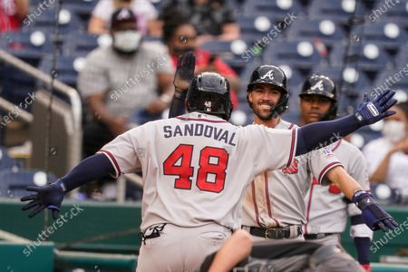 Atlanta Braves' Pablo Sandoval celebrates his two-run home run with Dansby Swanson, center, during the seventh inning of the second baseball game of a doubleheader against the Washington Nationals at Nationals Park, in Washington. The Braves won the second game 2-0