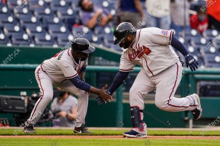 Atlanta Braves' Pablo Sandoval, right, celebrates his two-run home run with third base coach Ron Washington during the seventh inning of the second baseball game of a doubleheader against the Washington Nationals at Nationals Park, in Washington. The Braves won the second game 2-0