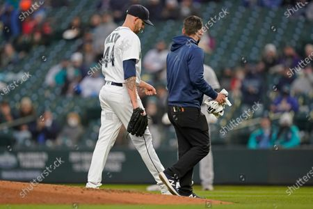 Seattle Mariners starting pitcher James Paxton, left, leaves the mound with a trainer during the second inning of the team's baseball game against the Chicago White Sox, in Seattle. Paxton was replaced by Nick Margevicius