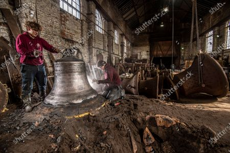 John Taylor & Co. continues a line of bell founding which has been unbroken since the middle of the 14th Century, when Johannes de Stafford was active only 10 miles from the site of the present foundry.From 1784 the business was operated by members of the Taylor family, and in 1839 it moved to Loughborough as a condition of a contract to recast the Parish Church bells. The Foundry was moved to its present site in Loughborough in 1859, and is now proud to operate the largest bell foundry in the world.Taylor's still make their bell moulds from the more labour intensive loam process as bell founders have done for centuries past. The making of the moulds takes a considerable amount of time as each layer is dried in a kiln overnight before the next is added, with all inscriptions and decoration being pressed into the final layer of wet loam as the mould is completed.  the worlds finest bell experts agree that the use of loam is a vital factor in producing the sweet toned bells for which the Foundry is known.Following traditional methods they also still dig a pit for each bell and bury  the moulds in the earth of the foundry floor before casting.  most bell founders abandoned the burying of their moulds to save time and money.  Taylors  are convinced that allowing the bell to cool slowly in the earth over a period of days gives a better molecular structure and a better sounding bell  Anthony Stone Foundry Foreman and his apprentice Sam Armistad cleaning the newly dug up Liberty bell  approx 1.2 tonnes in weight a quick clean before the the bell is tuned. This Liberty Bell is an exact copy of the original that was cast by the Whitechapel Foundry and Taylor's will have to add a 'crack' to the bell to make it an exact replica before it goes to the client in the USA