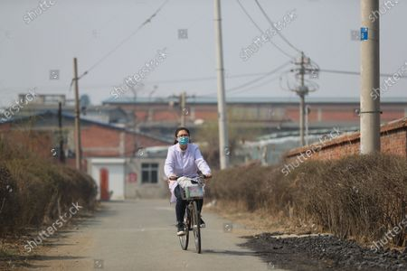 "Stock Picture of (210407) - SHENYANG, April 7, 2021 (Xinhua) - Sun Yi cycles to visit a patient at Qianyang Village, Donggang City of northeast China's Liaoning Province, April 6, 2021.   Sun Yi, born in 1997, works as a village doctor in Qianyang Village. After graduating from college majored in clinical medicine, she decided to return to her hometown and safeguard the health of the locals.    Qianyang Village has a population of over 14,000, where quite a number of people suffering from high blood pressure and diabetes. Some aged villagers are left behind by their children who work as migrant workers in other cities and cities. Sun visits these elders completed and is also responsible for data of health conditions for the villagers with spent. , she also holds health and publicicizes medical knowledge.   Sun is proud of her work. ""I grow up here and know many of the patients. I want to serve them with all I learnt and censor them a better and healthier life,"" She said."