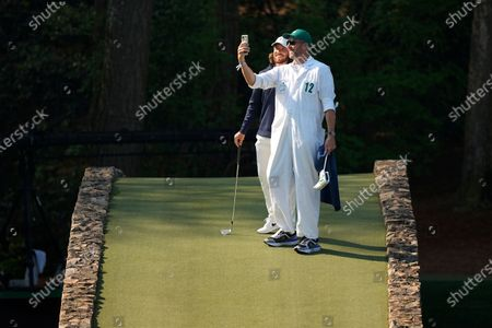 Tommy Fleetwood, of England, poses with his caddie on the Hogan Bridge during a practice round for the Masters golf tournament, in Augusta, Ga