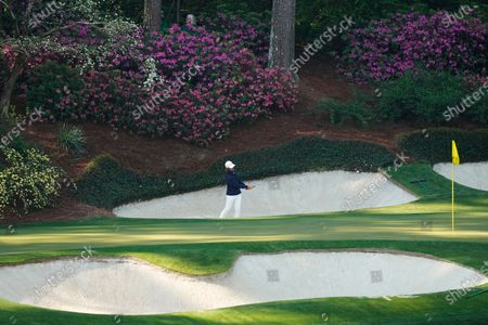 Tommy Fleetwood, of England, hits out of a bunker on the 12th hole during a practice round for the Masters golf tournament, in Augusta, Ga