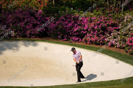 Webb Simpson hits out of a bunker at the 13th hole during a practice round for the Masters golf tournament, in Augusta, Ga