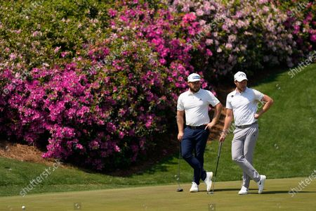 Tyrrell Hatton, of England, and Danny Willet, of England, wait to putt on the 13th hole during a practice round for the Masters golf tournament, in Augusta, Ga