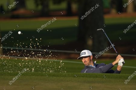 Michael Thompson hits out of a bunker during a practice round for the Masters golf tournament, in Augusta, Ga