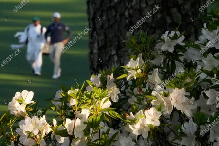 Michael Thompson walks with his caddie on the second fairway during a practice round for the Masters golf tournament, in Augusta, Ga