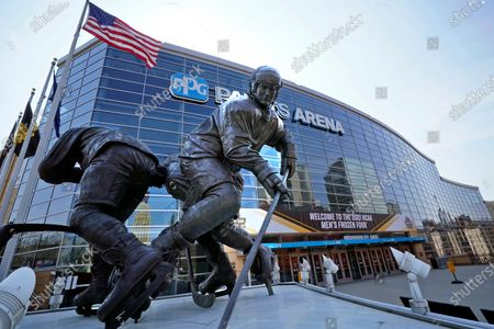 Stock Image of Statue of Pittsburgh Penguins Hockey Hall of Fame center Mario Lemieux, left, stands in front of the PPG Paints Arena, the site of the 2021 NCAA Men's Frozen Four collegiate hockey finals in downtown Pittsburgh