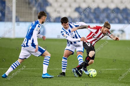 Stock Image of Adnan Januzaj and Martin Zubimendi of Real Sociedad CF competes for the ball with Iker Muniain of Athletic Club during the La Liga match between Real Sociedad CF and Athletic Club at Reale Arena on April 07, 2021 in San Sebastian, Spain.