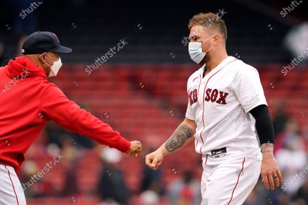 Boston Red Sox's Christian Vazquez, right, fist-bumps manager Alex Cora after the team's baseball game against the Tampa Bay Rays at Fenway Park, in Boston. The Red Sox won 9-2