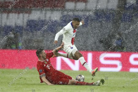 Bayern's Niklas Suele, left, tries to stop PSG's Kylian Mbappe during the Champions League quarterfinal soccer match between Bayern Munich and Paris Saint Germain in Munich, Germany