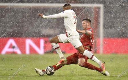PSG's Kylian Mbappe (L) in action against Bayern's Niklas Suele (R) during the UEFA Champions League quarterfinal, 1st leg soccer match between FC Bayern Muenchen and Paris Saint-Germain in Munich, Germany, 07 April 2021.