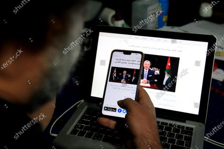 """A Jordanian follows the news on his mobile phone and his laptop after a statement was released by the King Abdullah II bin Al-Hussein, King of Jordan, in Amman, Jordan, 07 April 2021. King Abdullah II of Jordan addressed the Jordanians on 07 April, through a statement read on the news, he talked about the recent developments, following an alleged plot, the detention of several senior figures and a involving his half brother Prince Hamzah bin Hussein. The king announced the end of the crisis and said that Prince Hamza, is """"with his family at his palace, under my care,""""."""
